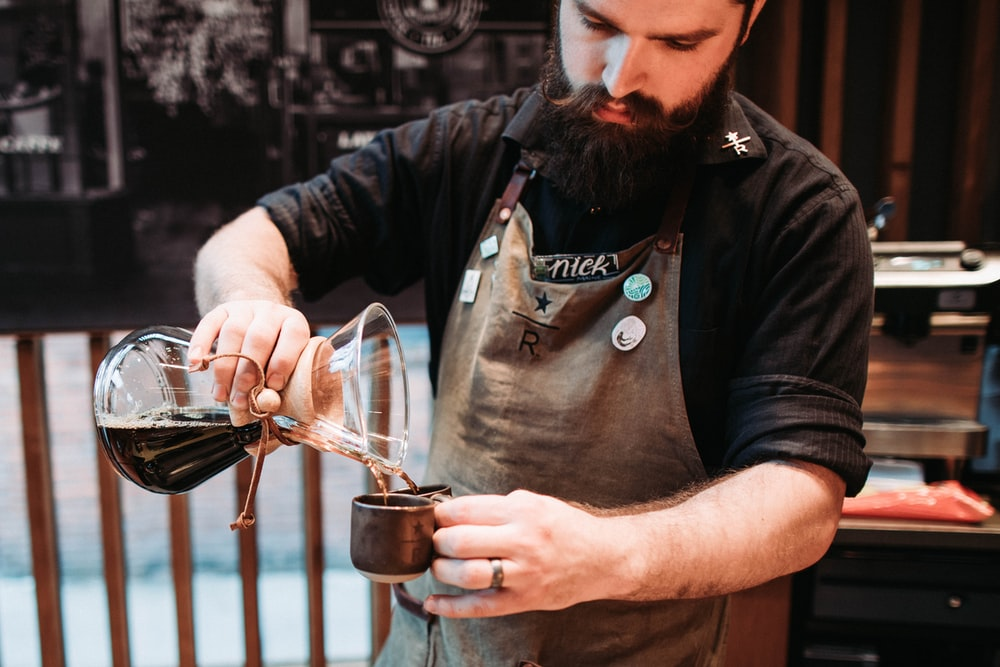 man pouring coffee on cup