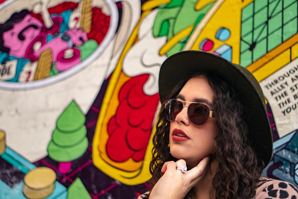 woman wearing black sunglasses and hat beside graffiti
