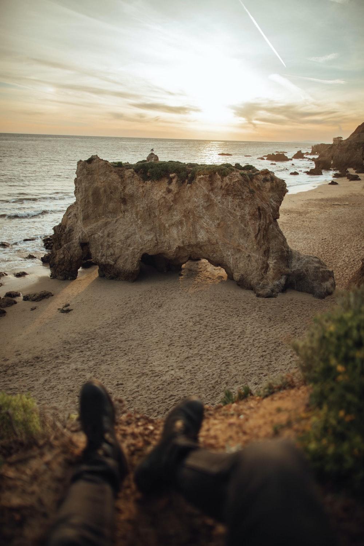 person sitting on cliff near beach