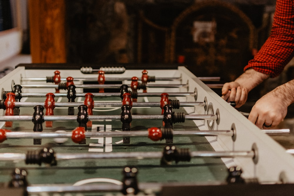 person playing foosball table