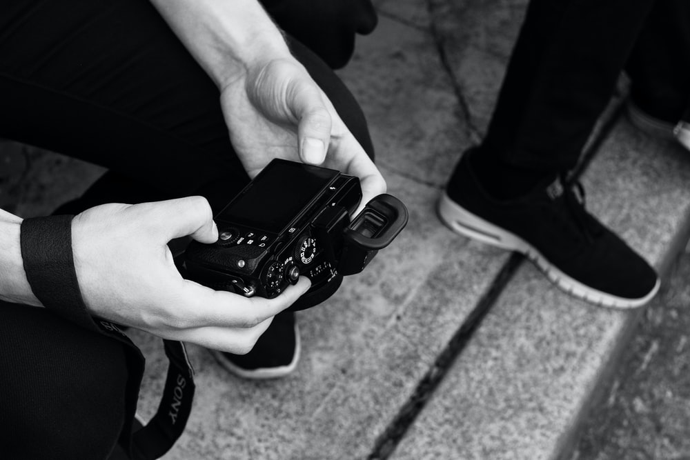 person holding digital camera while sitting