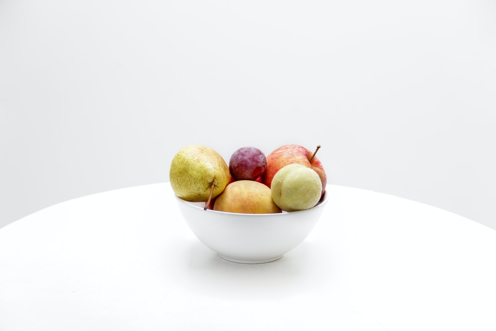assorted-color fruits on white ceramic bowl