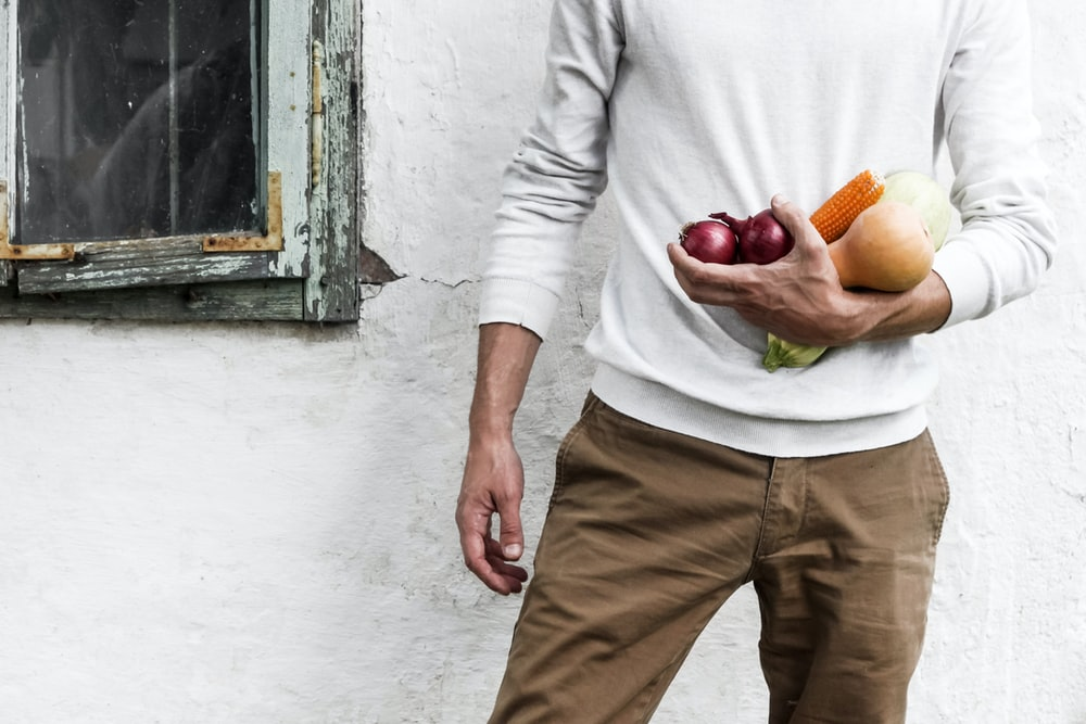 man standing beside white wall while holding fruits