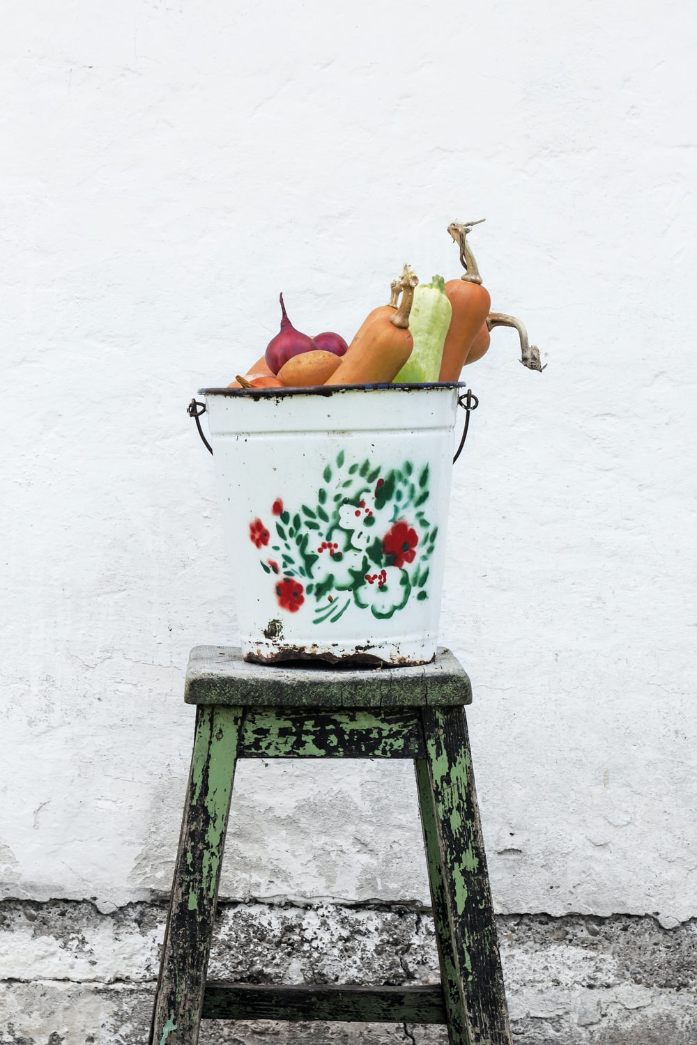 vegetables in white and multicolored floral bucket on green wooden stool