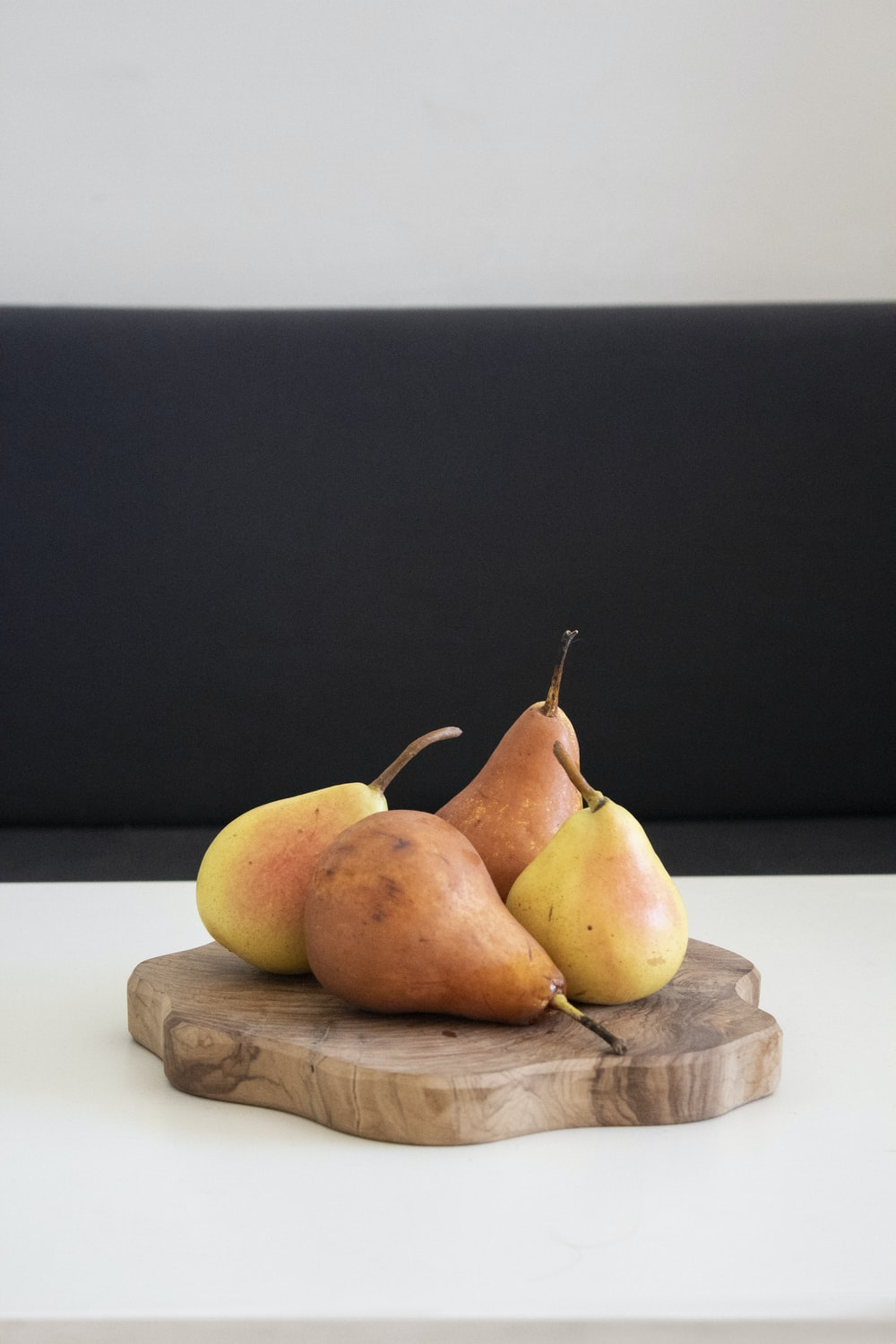 four orange pears fruits on brown wooden board panel