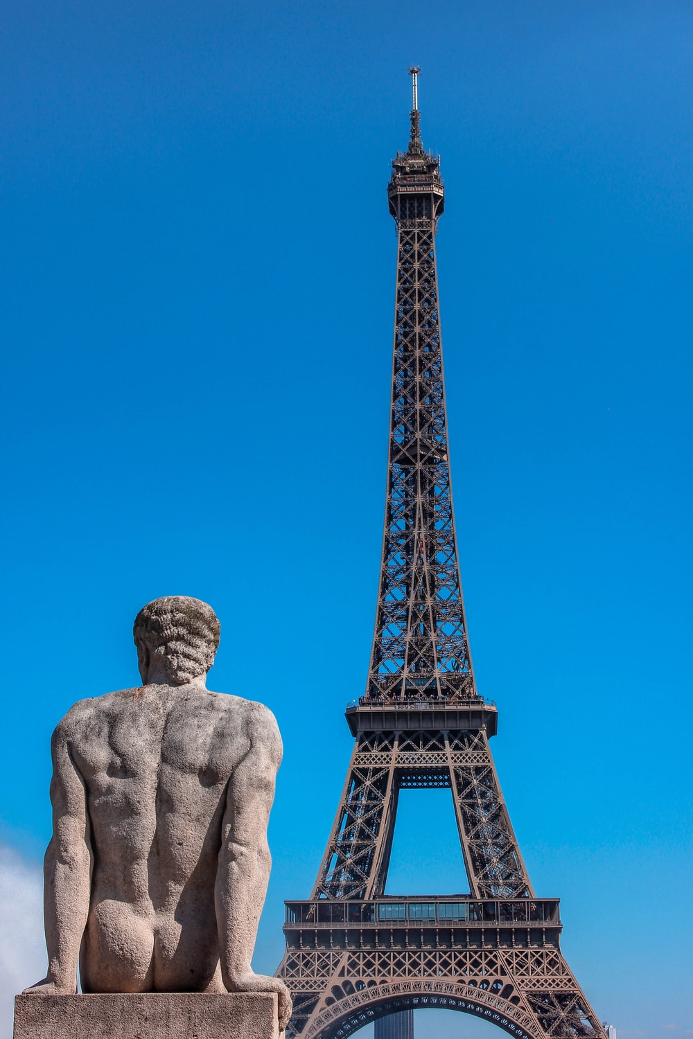man's sculpture and Eiffel Tower