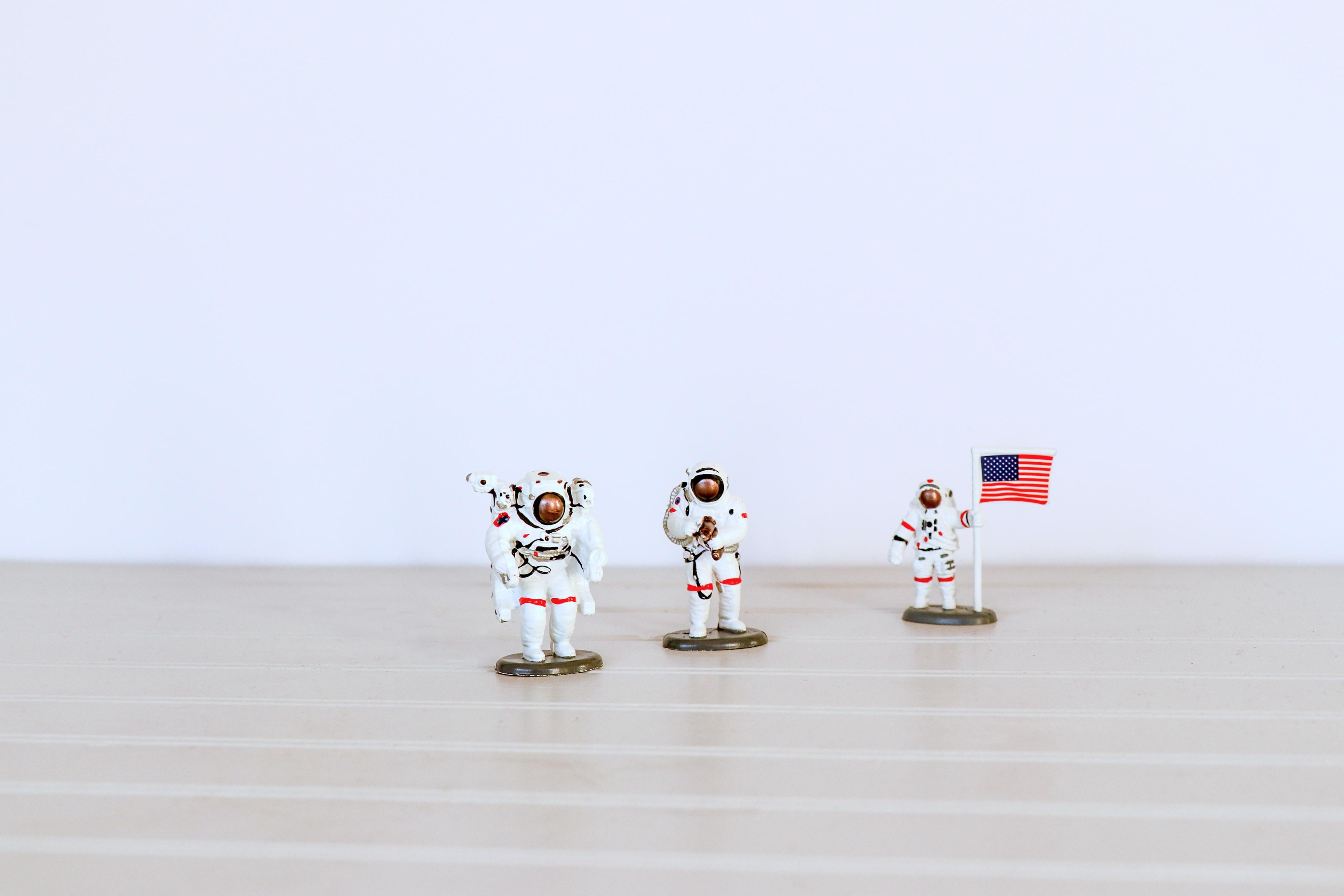 three astronaut figures on gray surface