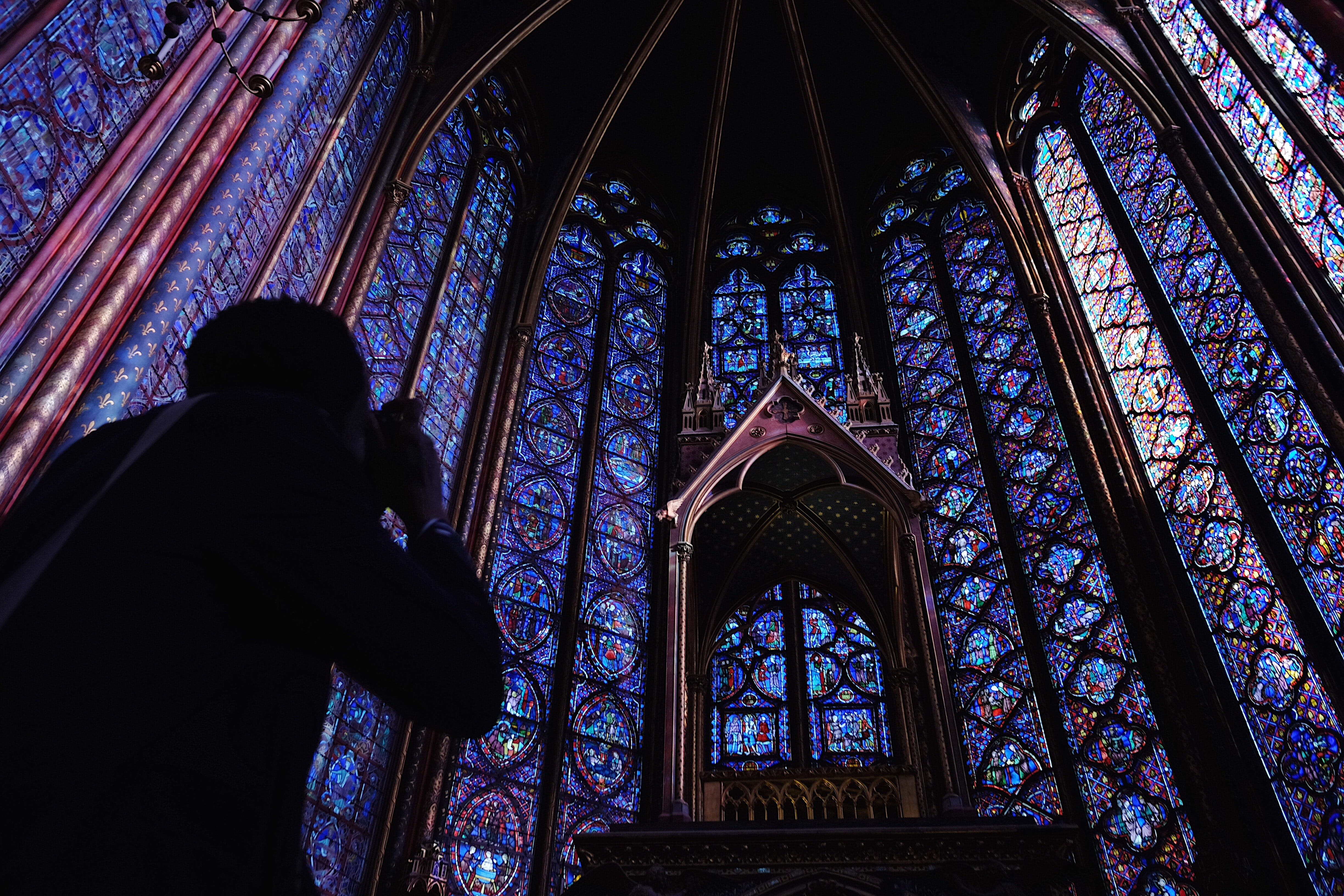 silhouette of person holding camera taking picture cathedral interior