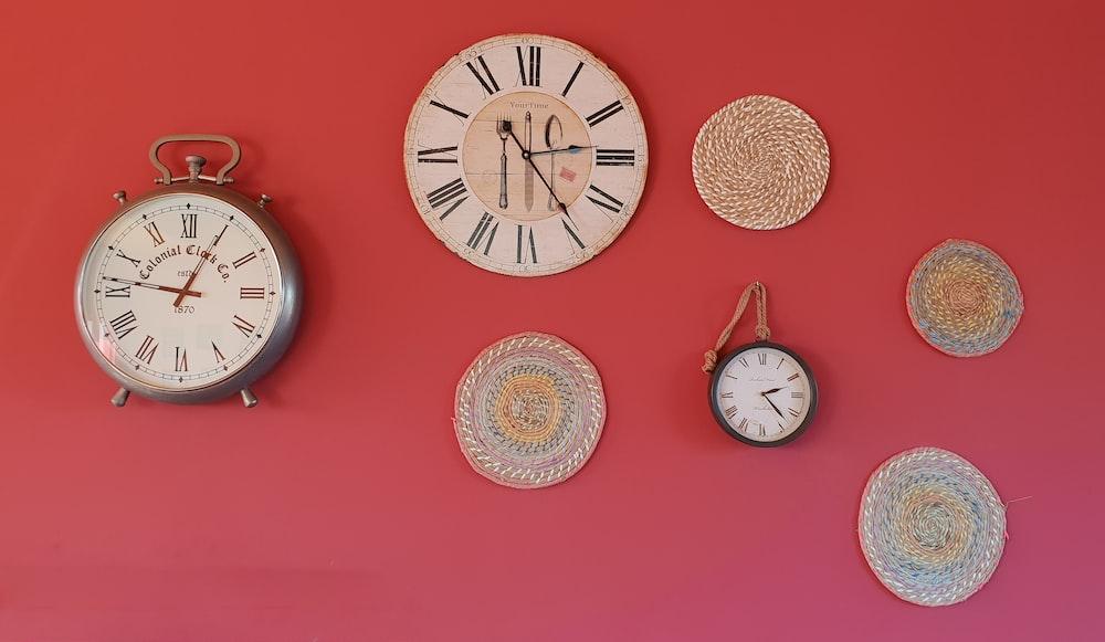 three round analog clocks and round gray mats