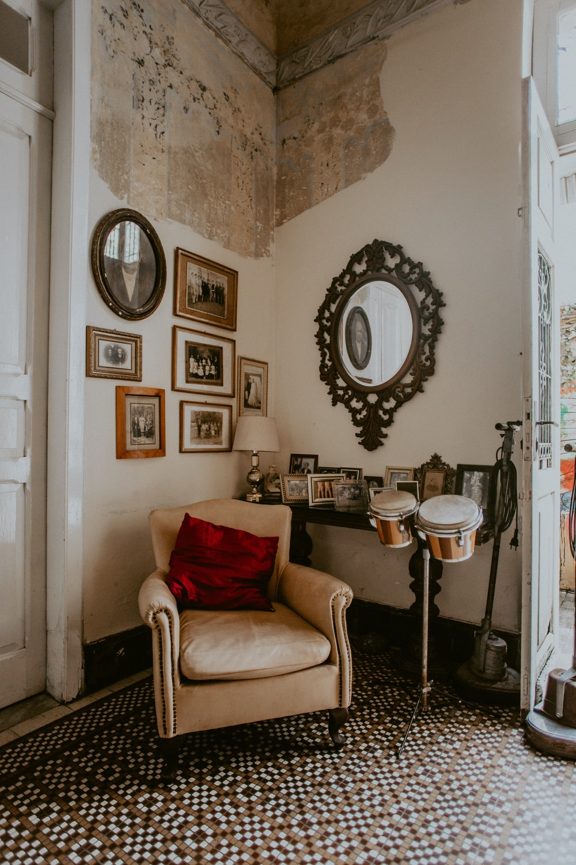 brown fabric sofa chair beside white wall