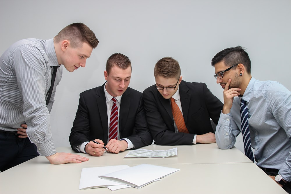 four men looking to the paper on table