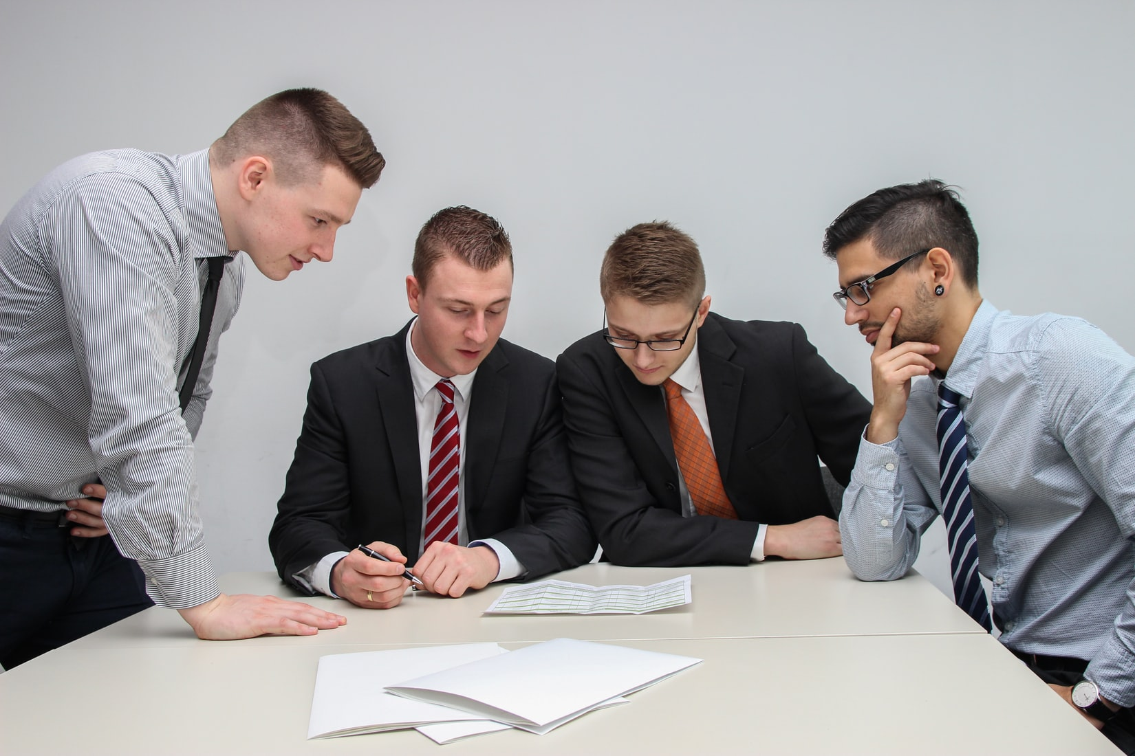 business men sitting around a white table looking at a document.