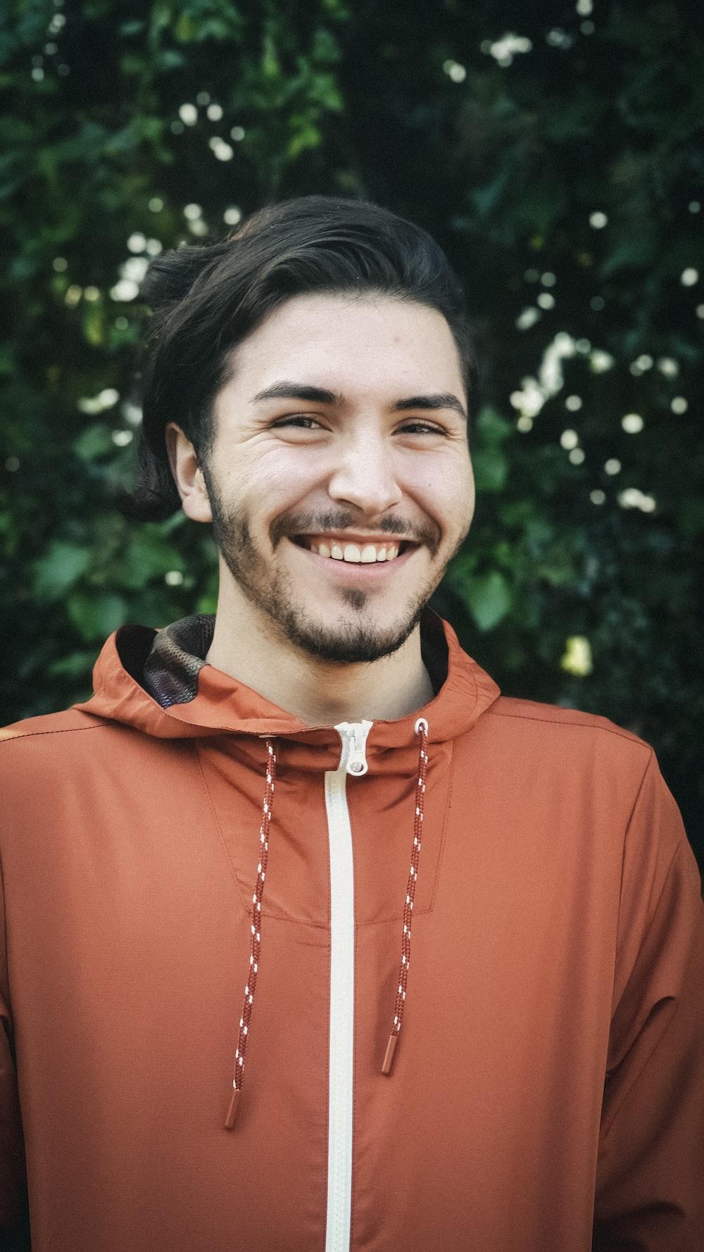 smiling man wearing orange zip-up jacket