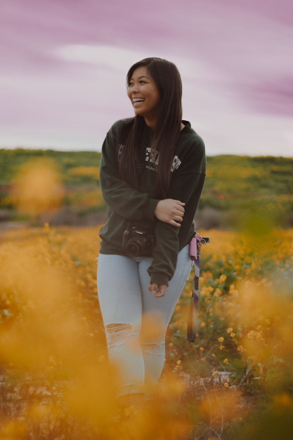 woman in black jacket and blue denim fitted jeans standing in middle of flower field smiling during daytime