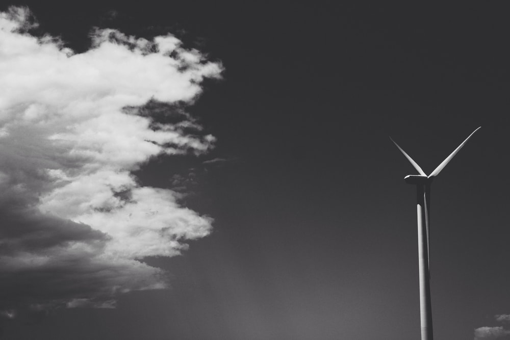greyscale photo of windmill under cloudy sky