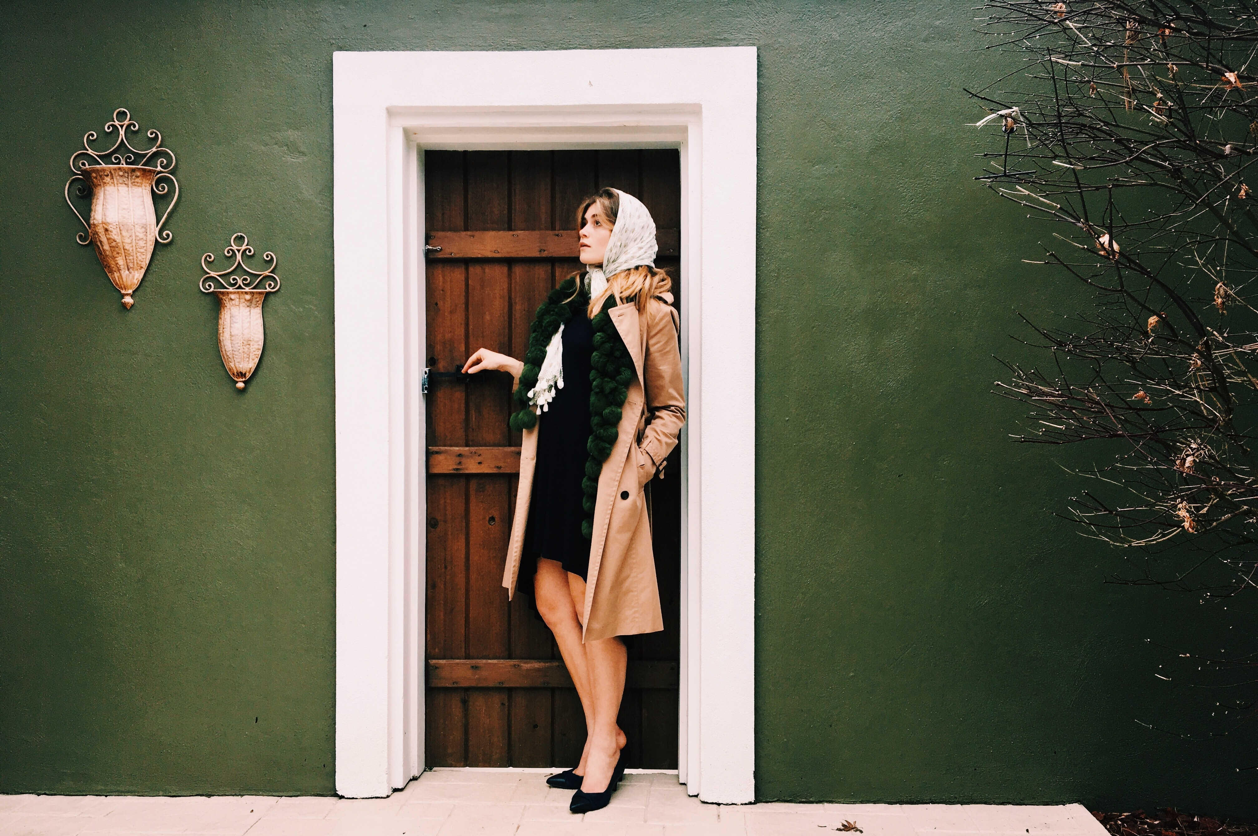 woman standing beside door during daytime