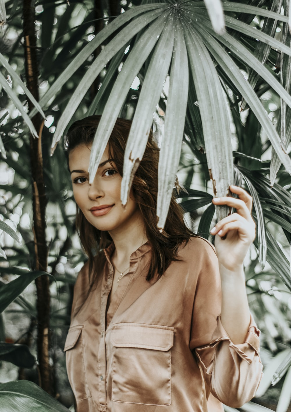 woman in brown shirt stands under palm fronds