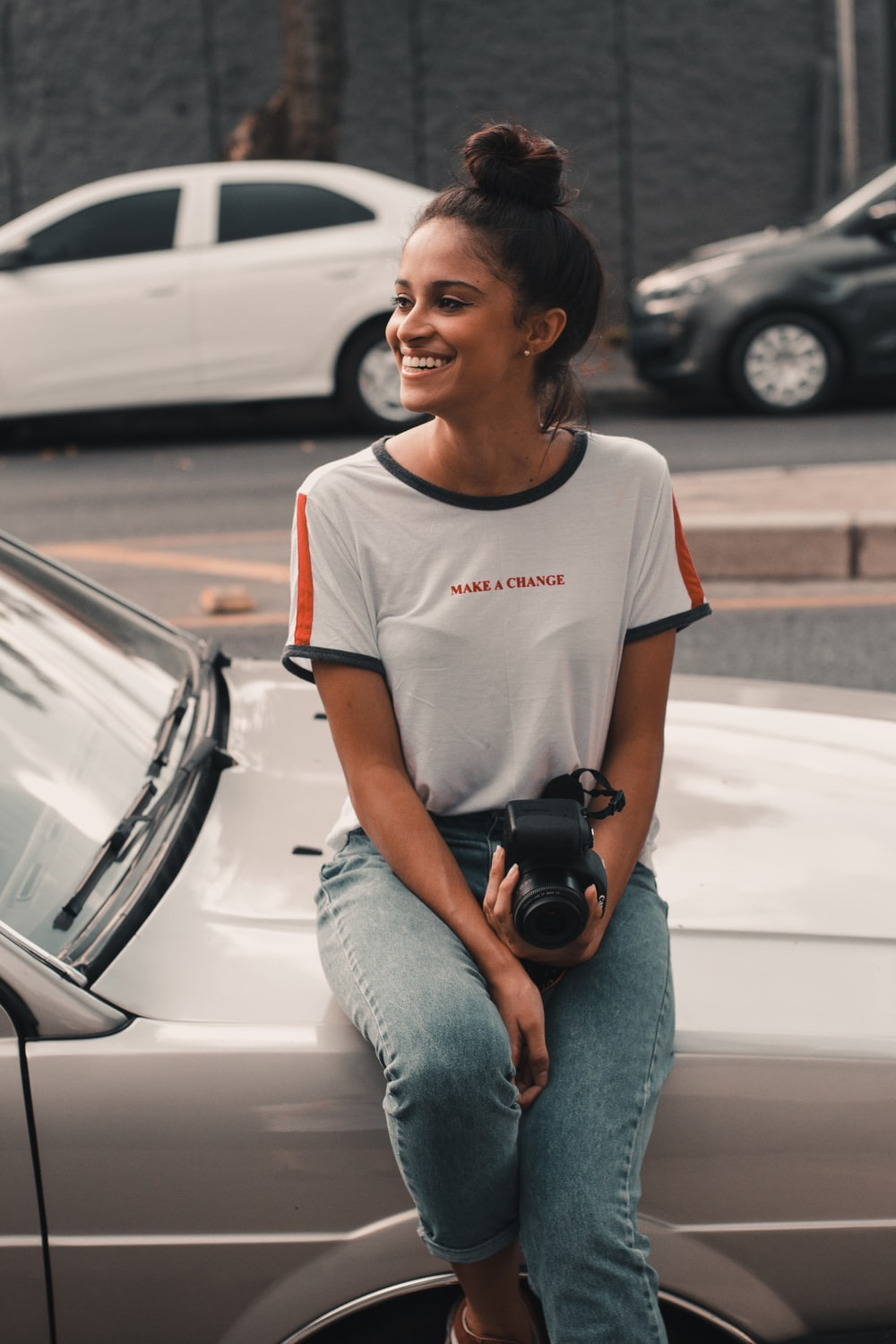 smiling woman sits on car hood holding camera