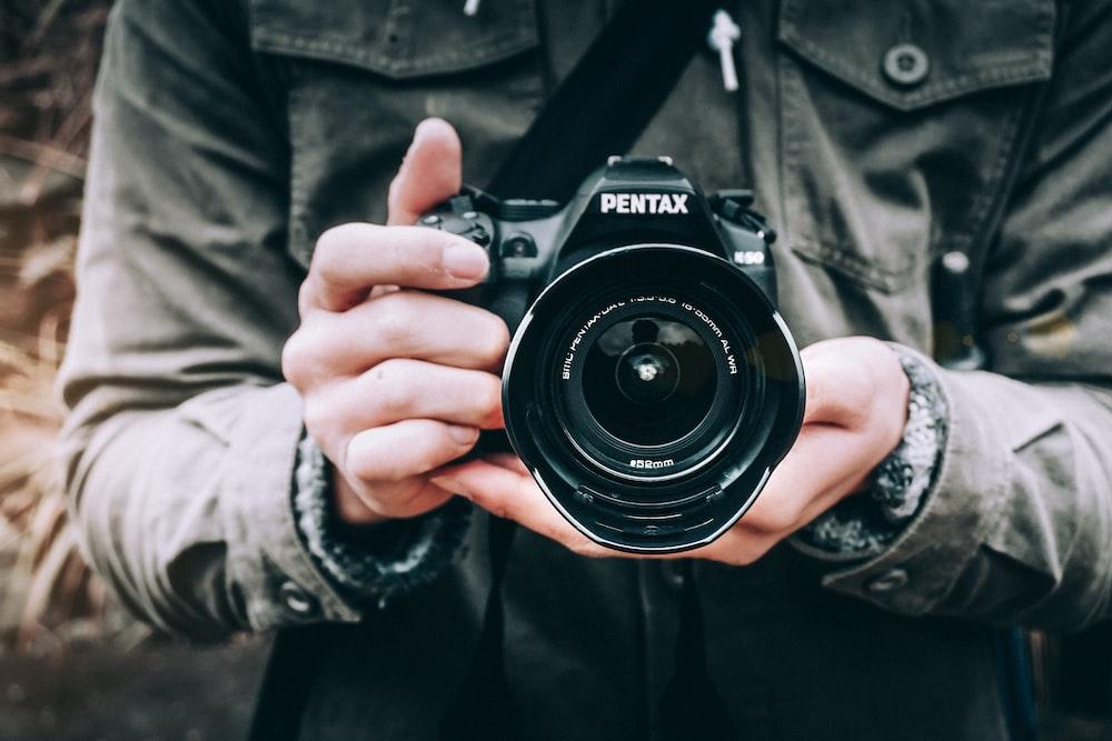 person holding black Pentax DSLR camera