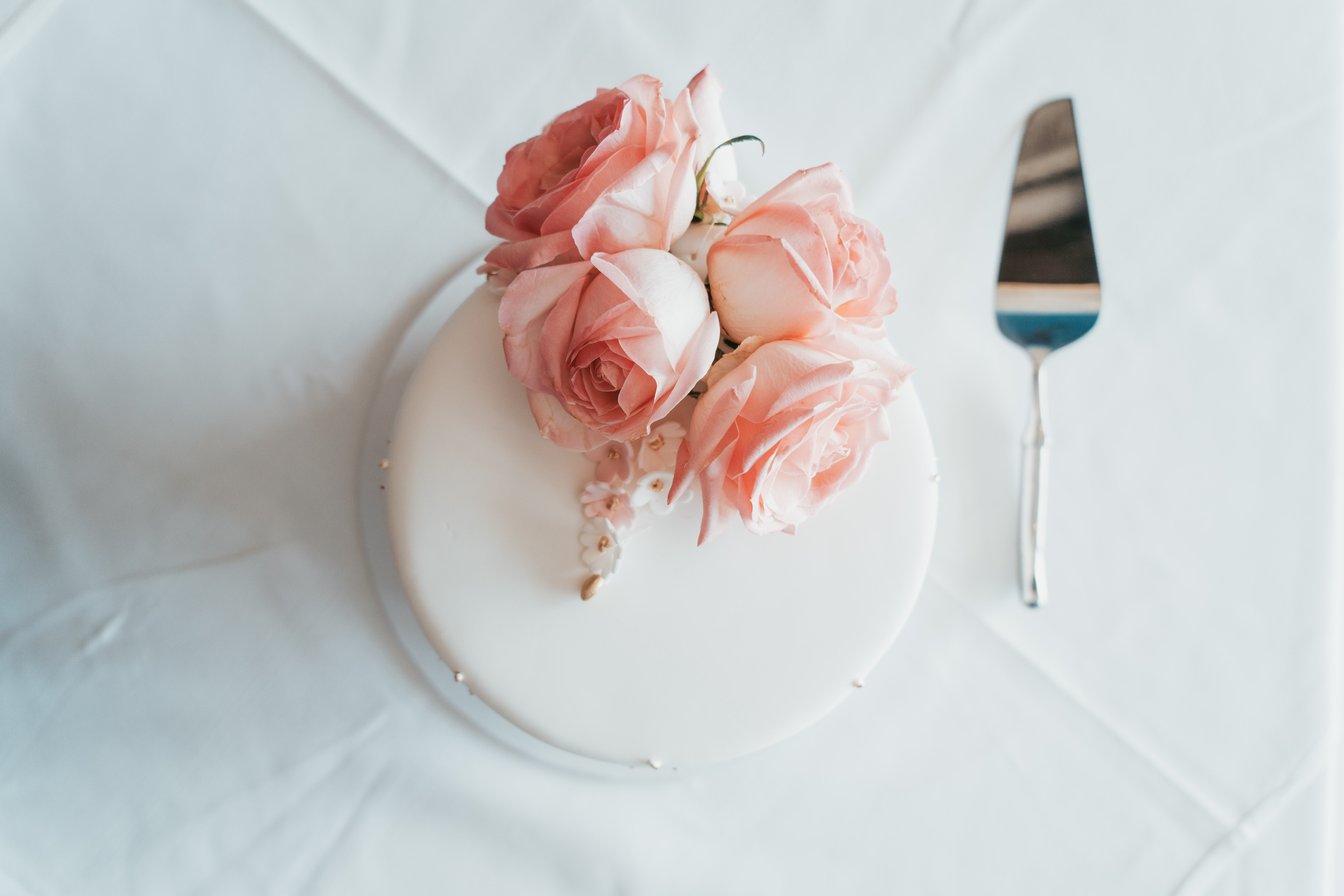 round fondant cake with white icings and roses toppings beside cake server on white textile