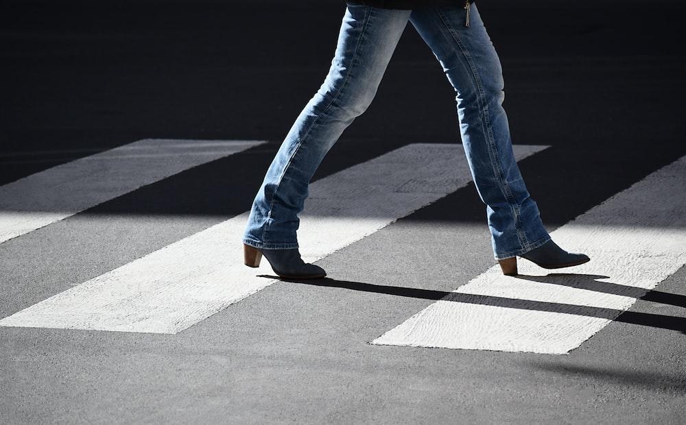 person wearing jeans walking at pedestrian lane