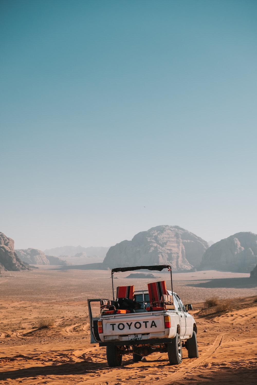 white Toyota crew-cab truck on desert during daytime
