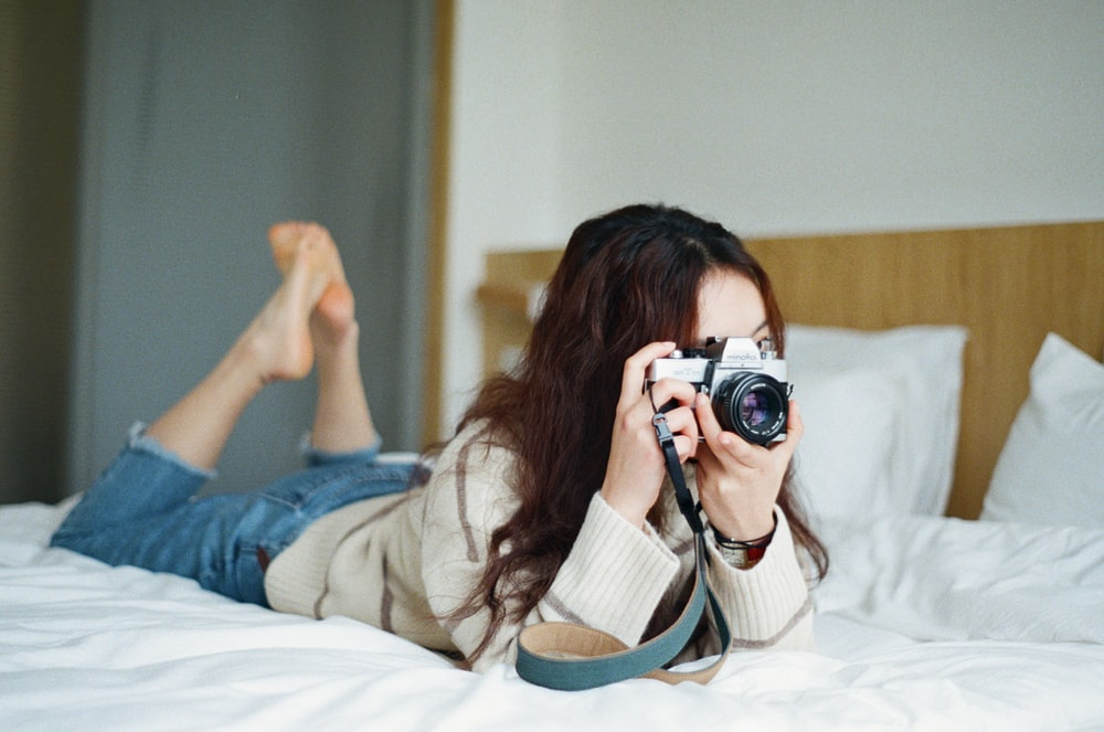 woman on bed taking picture with SLR camera