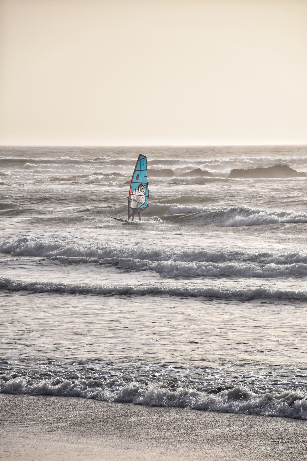 person playing sail boat on beach waves