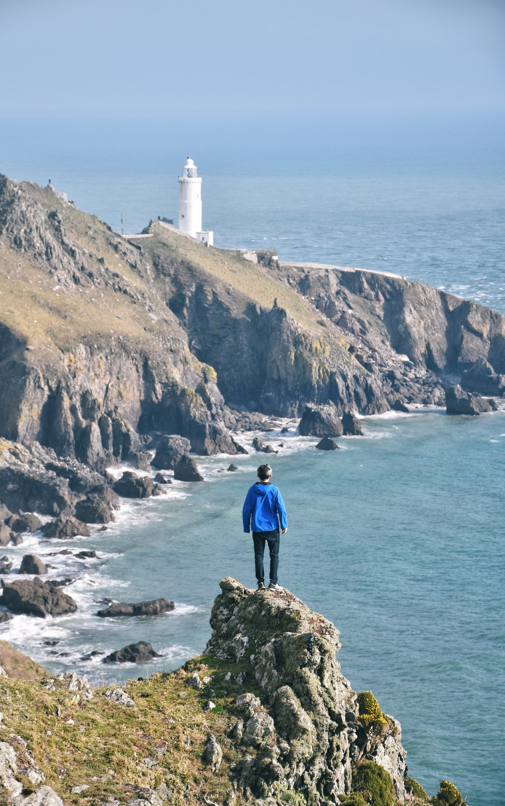 man standing on rock with view of lighthouse and ocean
