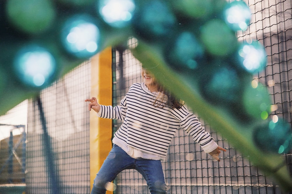 girl wearing white and black striped long-sleeved shirt playing in playground during daytime