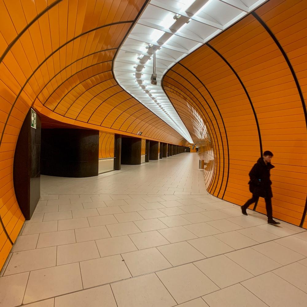 person wearing black coat walking inside brown painted wall