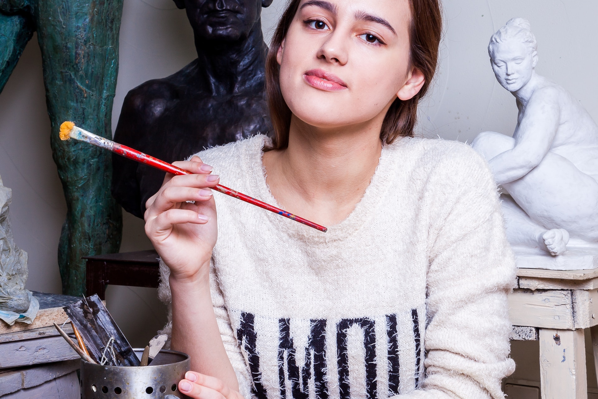 woman leaning on table and holding paint brush