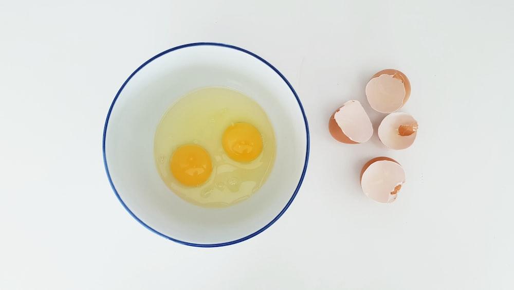 two cracked eggs in bowl beside egg sheels