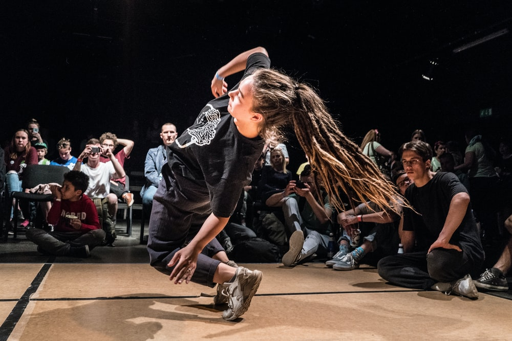 woman dancing in front of people sitting on floor