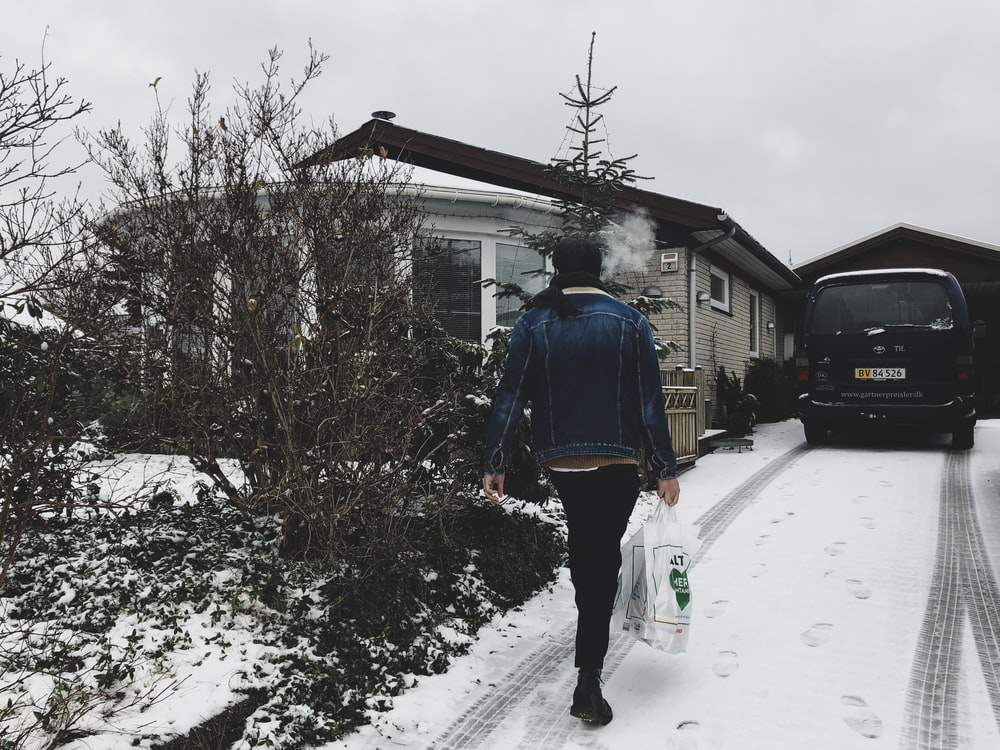woman carrying plastic bag walking near house during winter