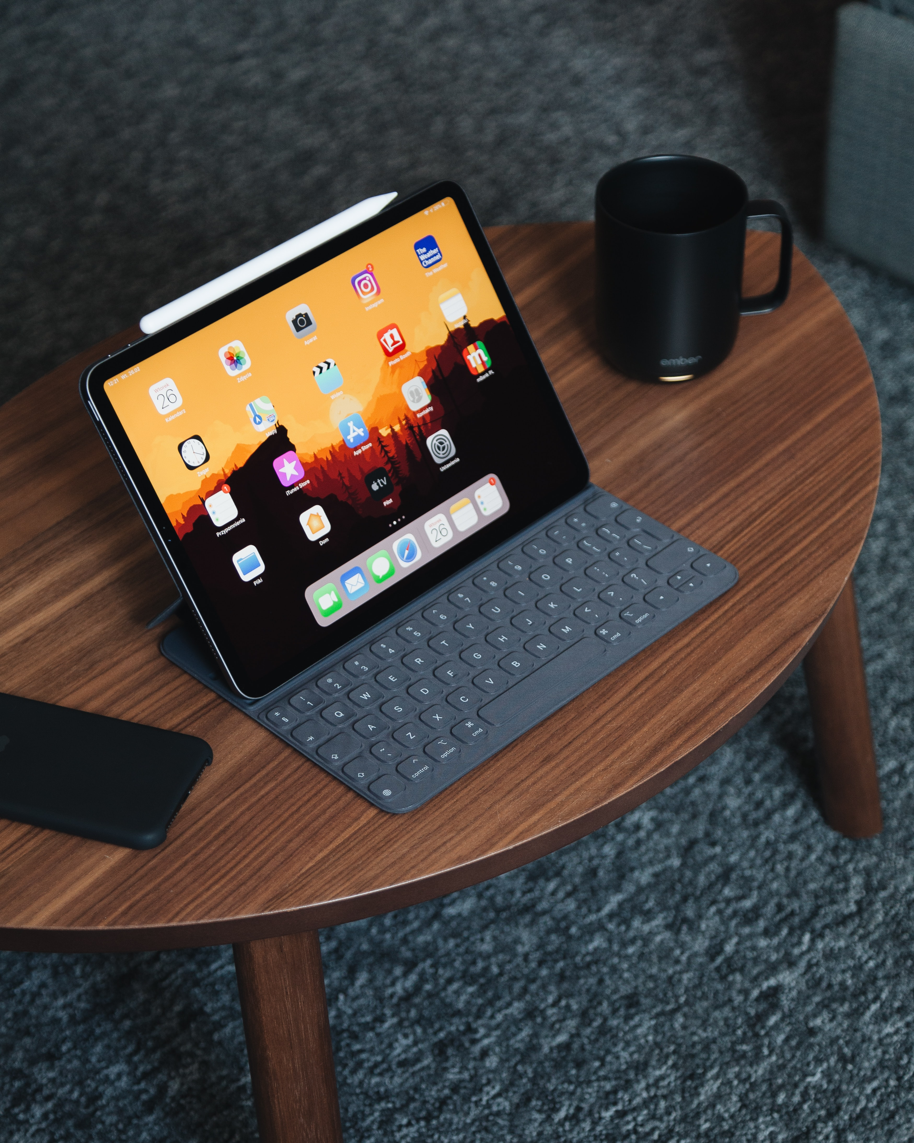 black tablet computer with gray portable keyboard on brown wooden coffee table