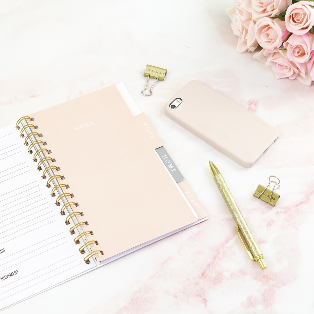 gold smartphone and pink book