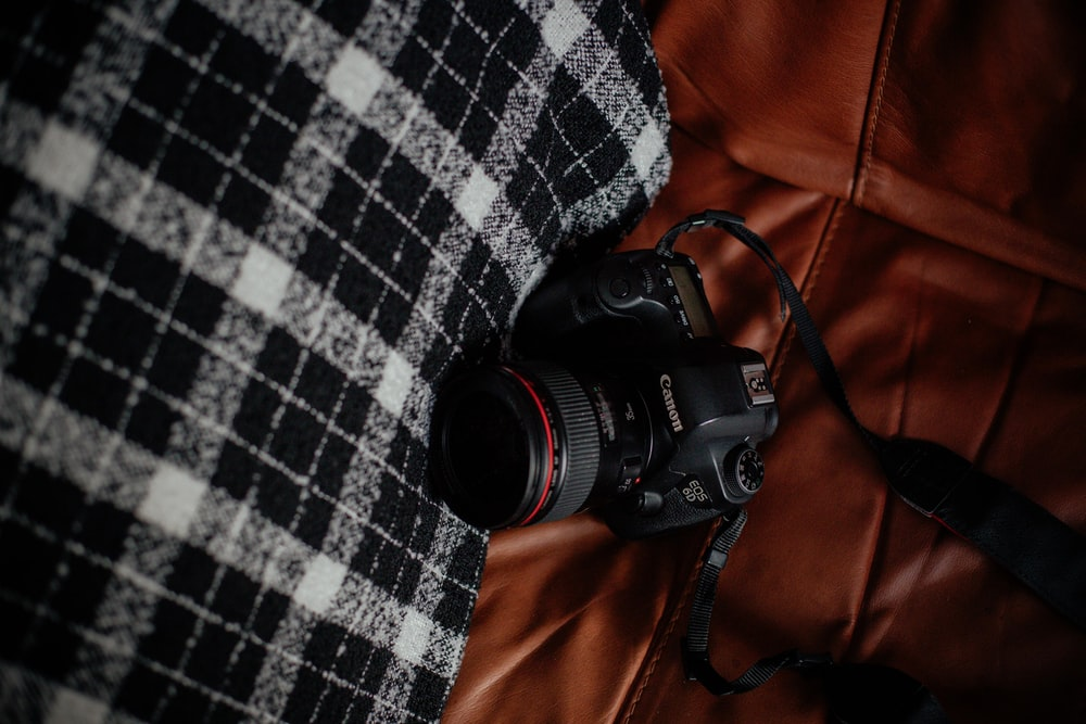 black Canon SLR camera on brown textile
