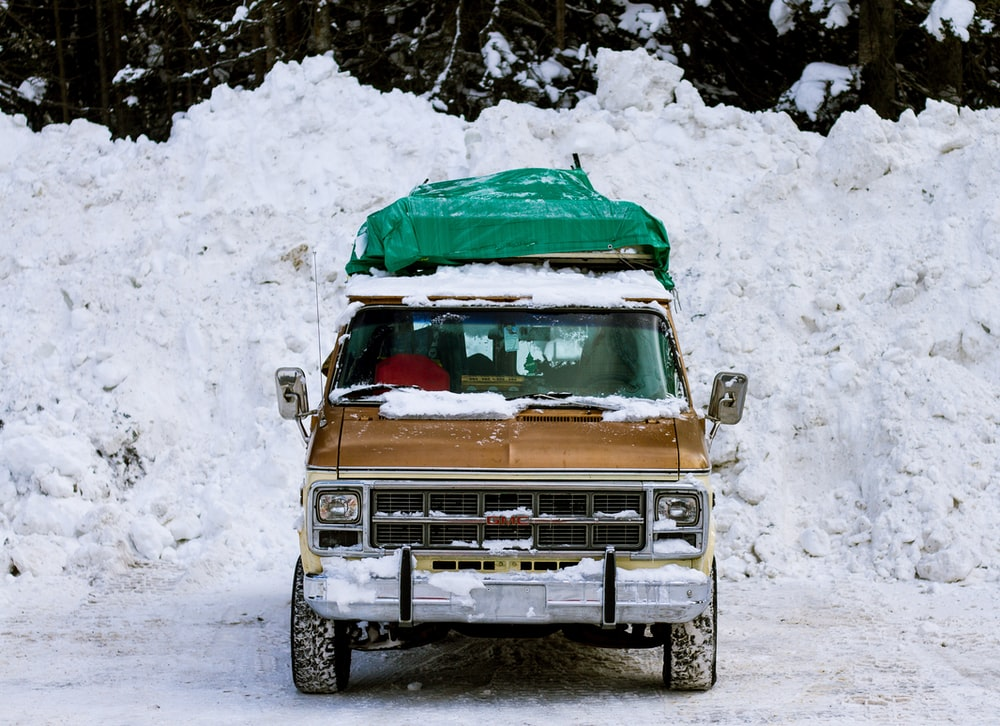 brown truck parked on snow covered ground during daytime