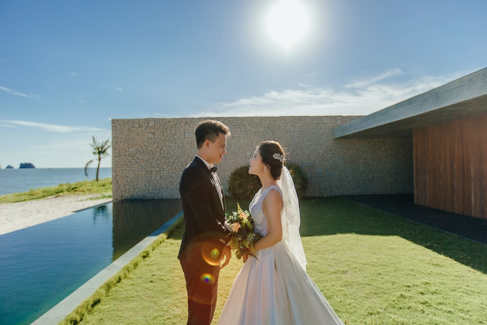 man and woman wearing wedding dresses standing beside body of water