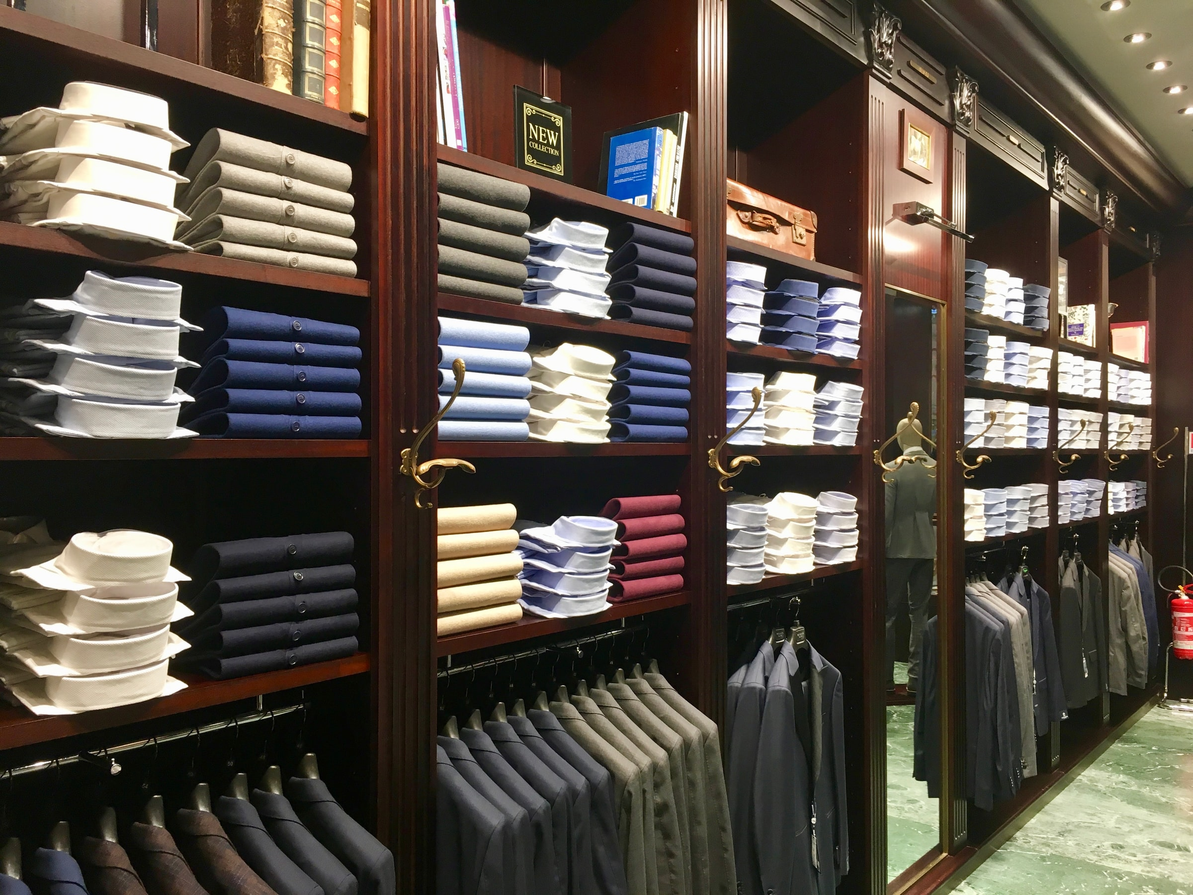 assorted-colored clothes on brown wooden shelf
