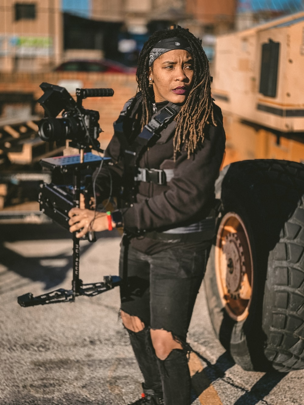 woman wearing black ripped jeans holding camera