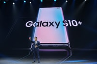 man standing beside projector screen with black Samsung Galaxy S10+ text