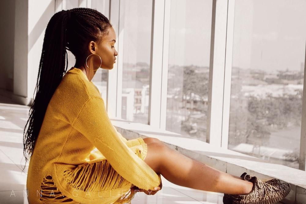 woman wearing long-sleeved dress sitting near window