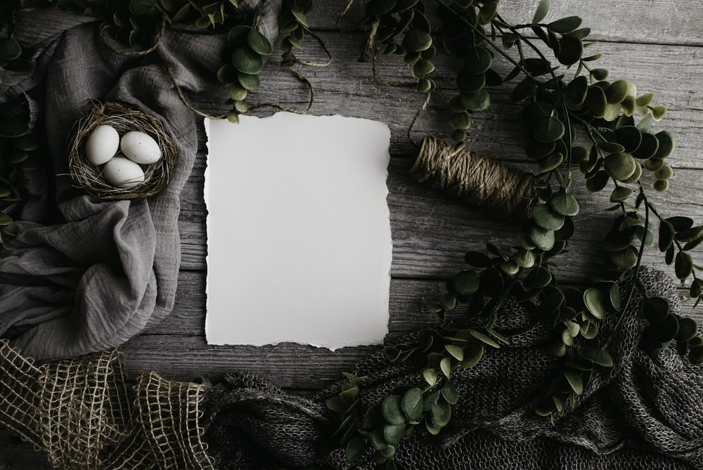 an easter flatlay of white paper and easter eggs in a nest
