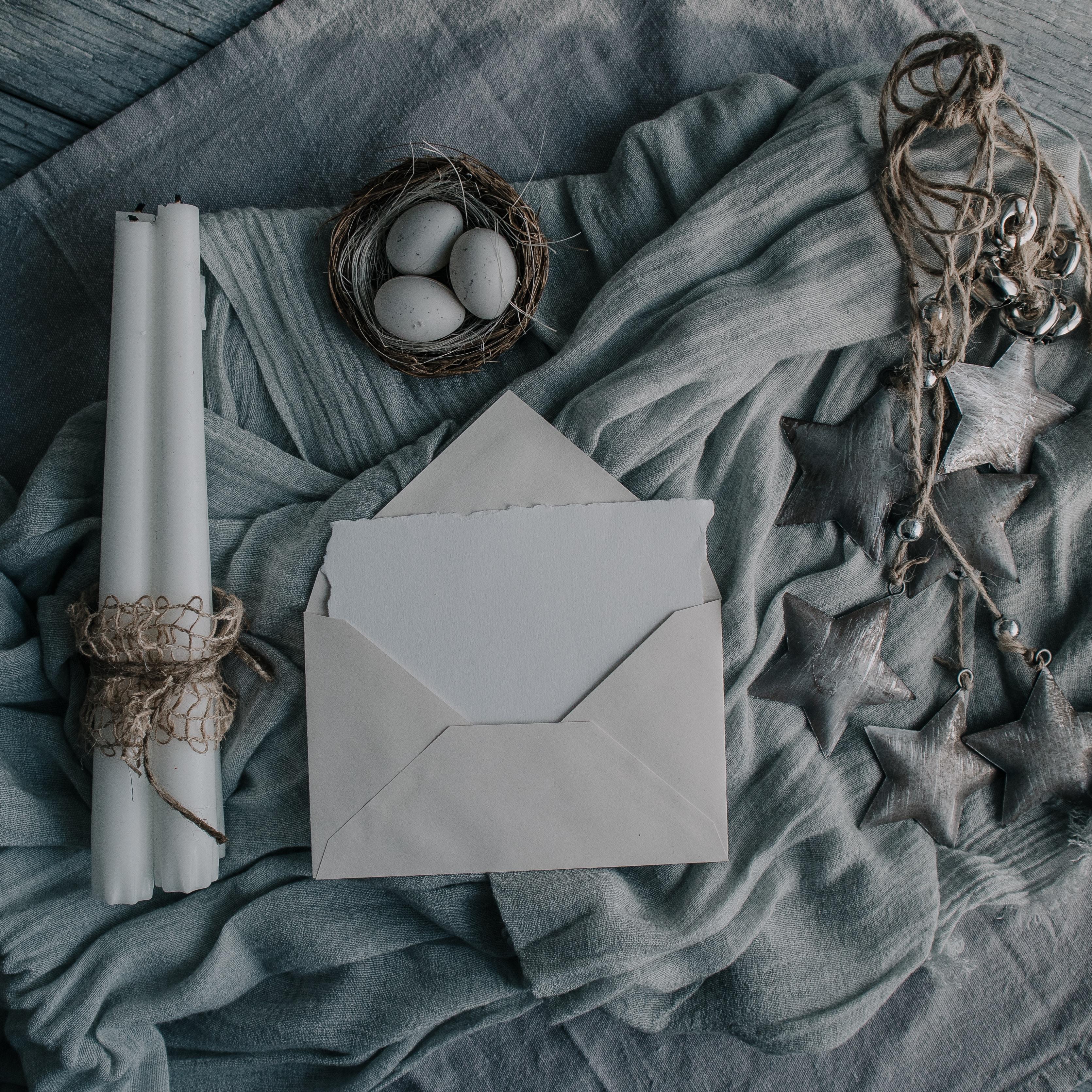 white envelop nearby white candle sticks