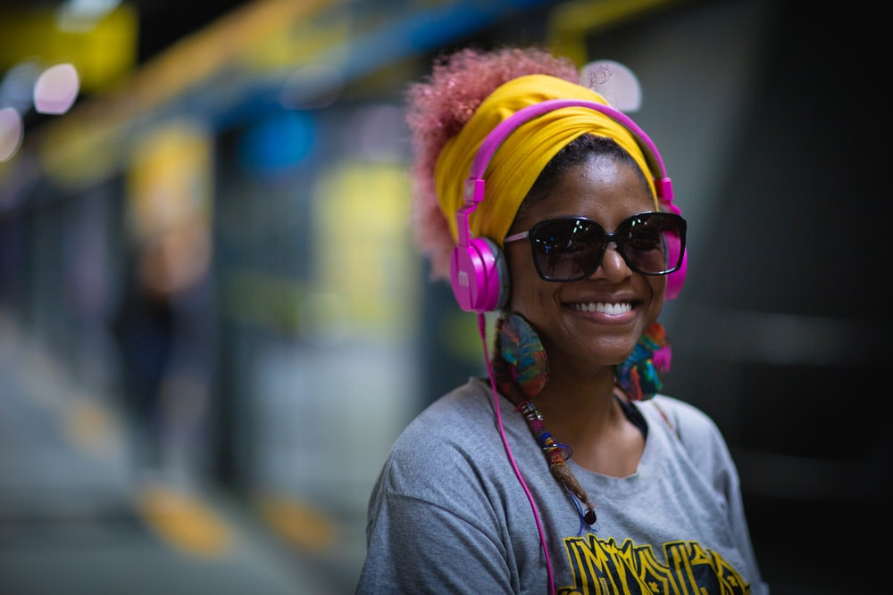 smiling woman wearing sunglasses in train station selective focus photography