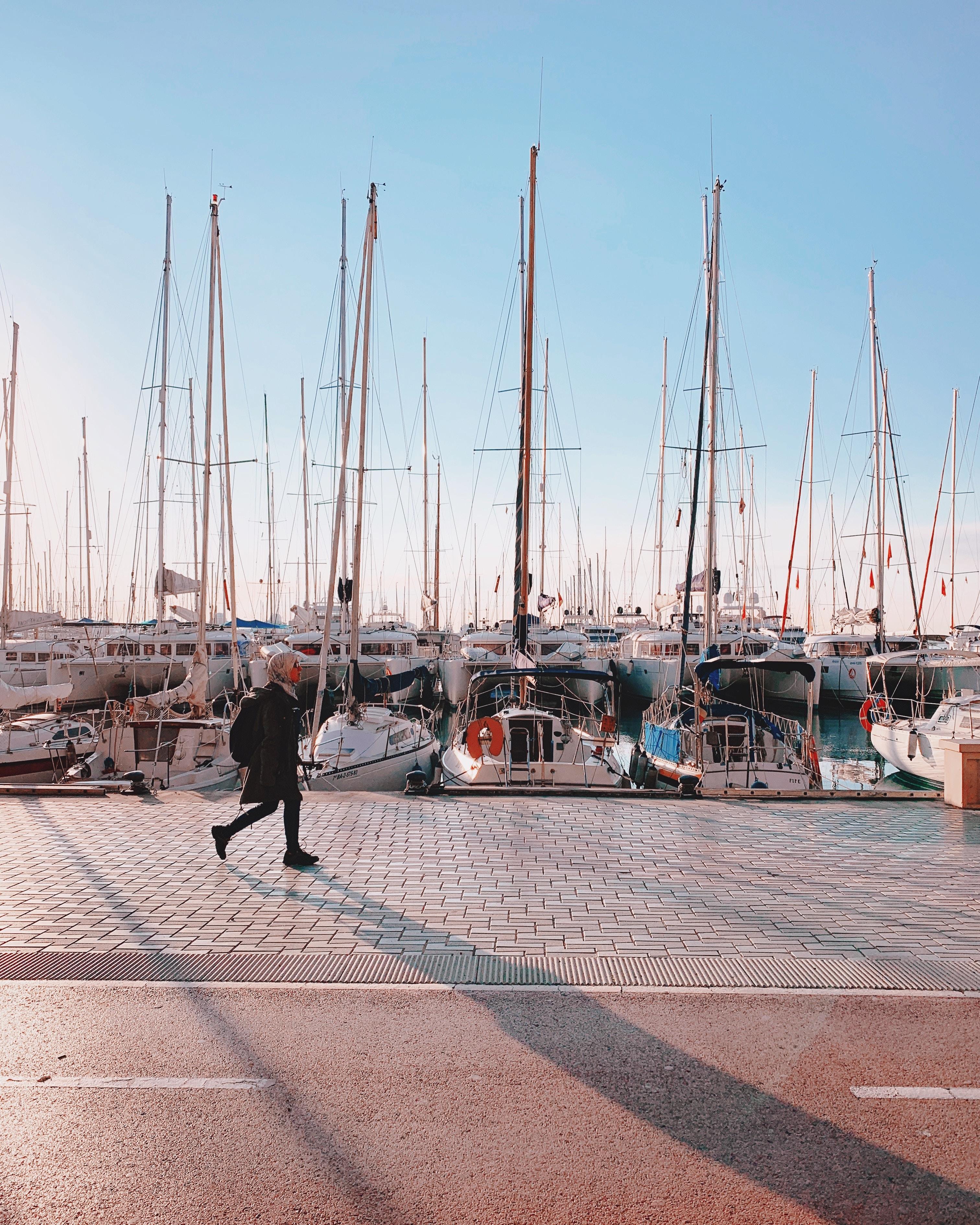 woman walking beside boats