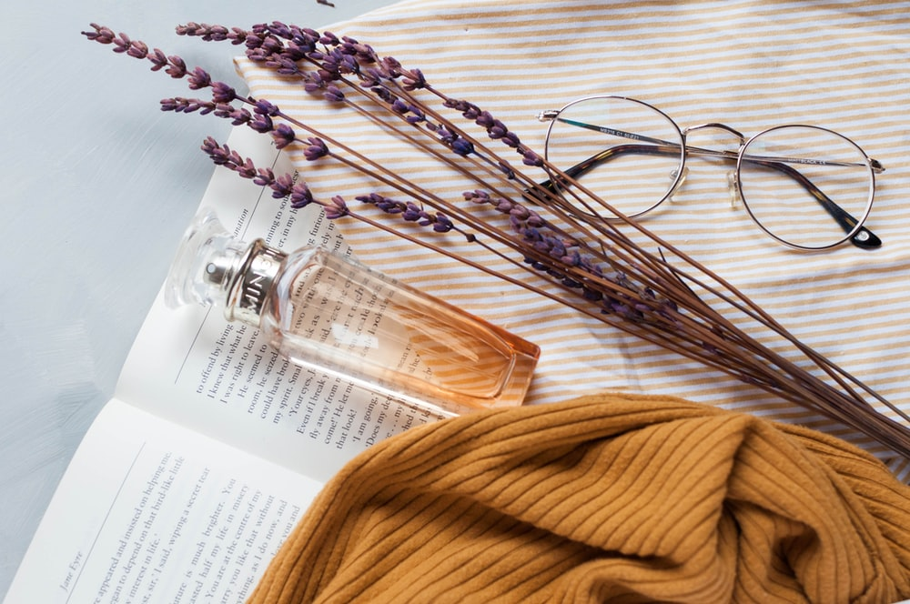fragrance bottle, lavender, and eyeglasses