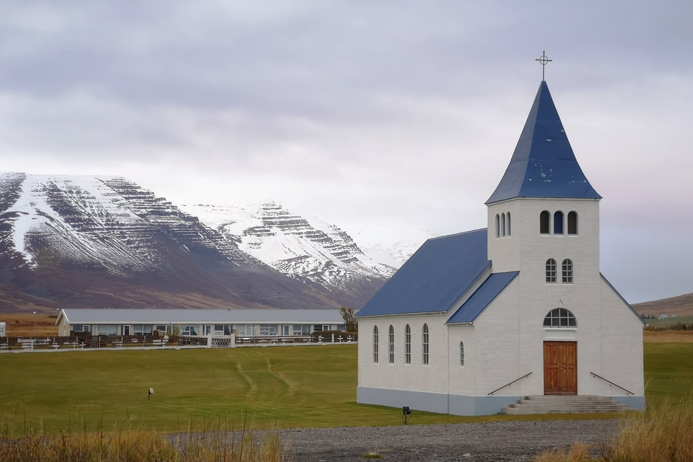 white and blue church across mountain